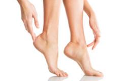 Closeup shot of a woman applying moisturizer to her leg and feet